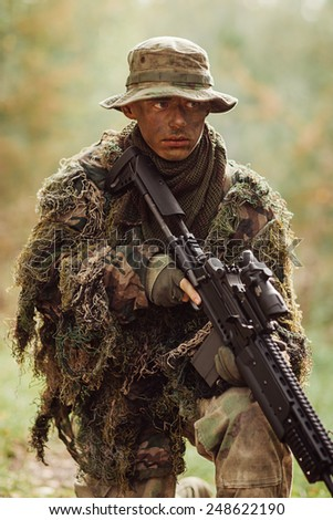 soldier stands with arms in wood and looks forward - stock photo