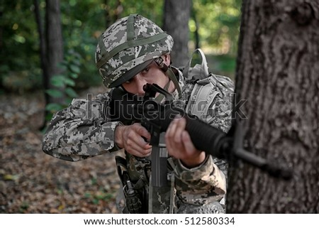 Soldier taking aim from rifle in forest, close up view