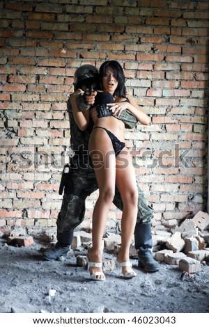 Soldier taking frightened woman in underwear hostage - stock photo