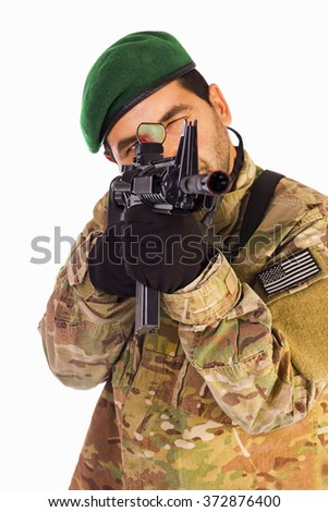 Soldier to aim and shoot at a target with assault riffle isolated on white background with green beret, black gloves and multicam uniform. - stock photo