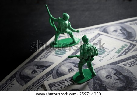 Soldier toys on money. - stock photo