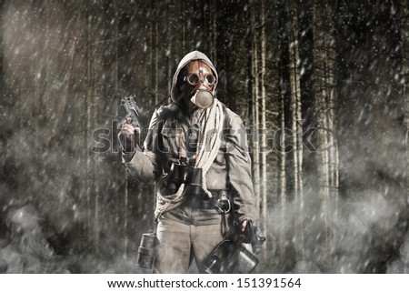 Soldier wearing a gas mask is fighting in a forest