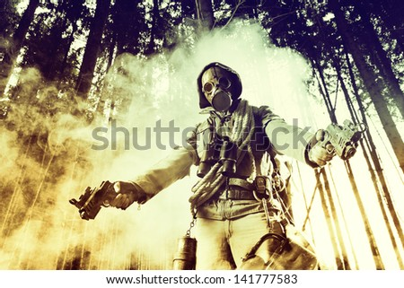 Soldier wearing a gas mask posing with two guns
