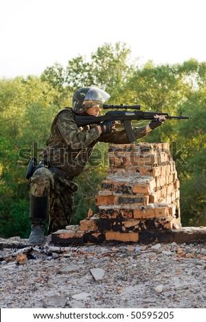 Soldier with a machine gun in an ambush - stock photo
