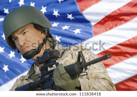 Soldier with assault rifle in front of US flag - stock photo