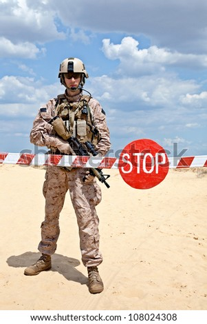 Soldier  with assault rifle near the barrier at a checkpoint - stock photo