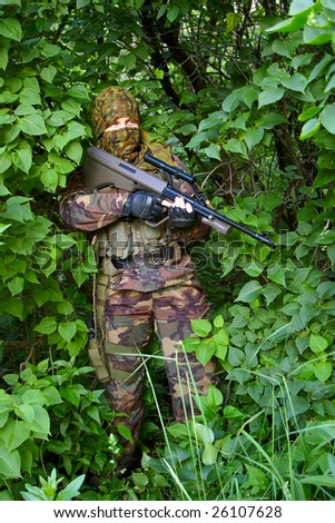 soldier with assault rifle on the nature