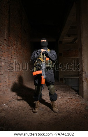 Soldier with automatic AK-47 rifle in black mask and bulletproof vest posing in ruins of urban building