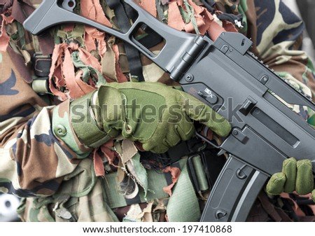 Soldier with camouflage suit holding weapon - stock photo