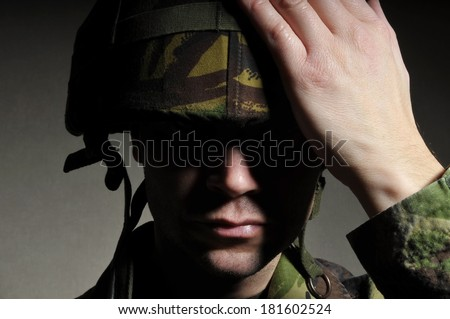Soldier With Face In Shadow - stock photo