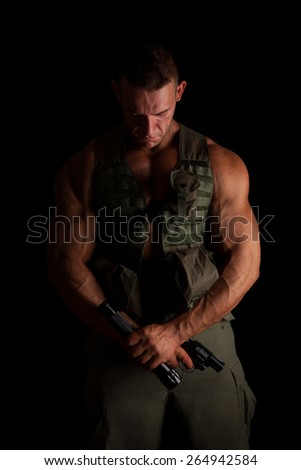 Soldier with gun and flashlight in green uniform standing proud isolated on black background. Army, security and protection. - stock photo