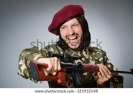 Soldier with handgun against gray - stock photo