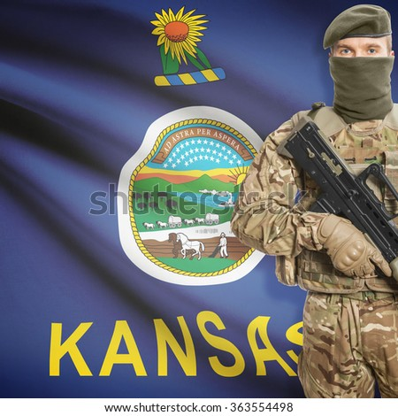 Soldier with machine gun and USA state flag on background series - Kansas - stock photo