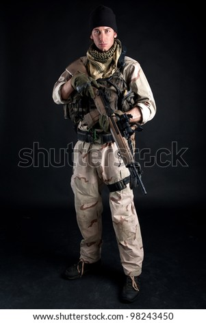 Soldier with rifle against black background. Full body. - stock photo