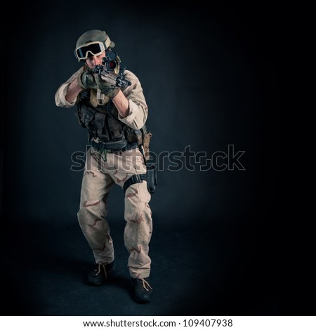Soldier with rifle against black background. Full body and copy - stock photo