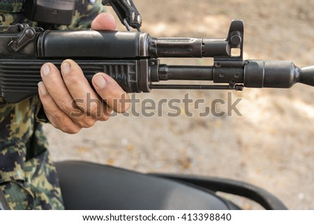 Soldier with rifle against blur background. Shallow depth of field.