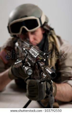 Soldier with rifle against white background. Shallow depth of field. - stock photo
