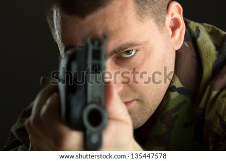 Soldier with rifle AK-47 aiming to you - stock photo