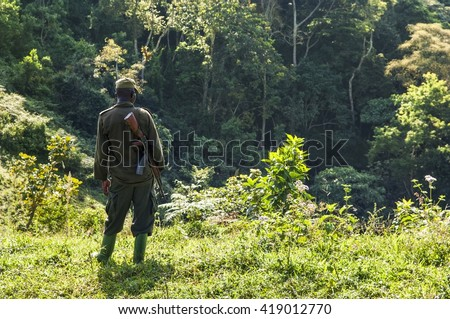 Soldier with rifle AK-47 in african jungle.
