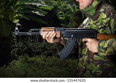 Soldier with rifle AK-47 in jungle - stock photo