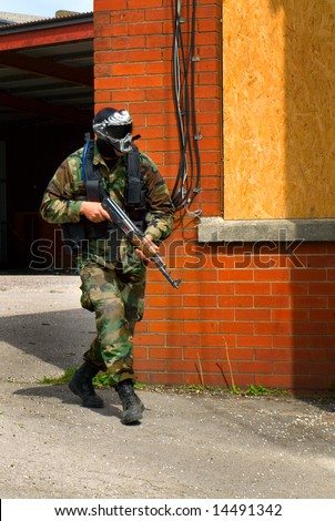 Soldier with Rifle and Face Mask By Brick Wall