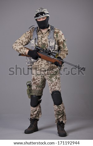 Soldier with sniper rifle posing over grey background - stock photo