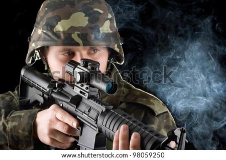 Soldier with the smoking gun in studio. Closeup - stock photo