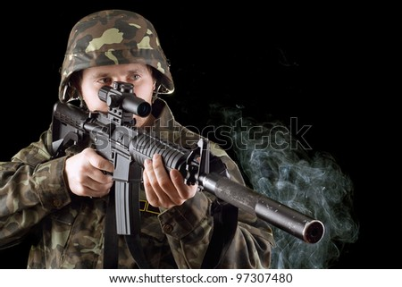 Soldier with the smoking gun in studio. Isolated - stock photo