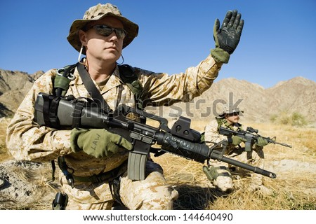 Soldier with weapon signaling during a battle - stock photo