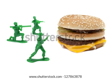 Soldiers aiming their weapon at a giant hamburger sandwich - stock photo