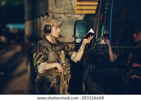 soldiers at the checkpoint stopped for document checks - stock photo