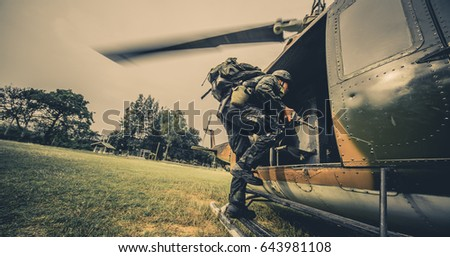 Soldiers boarding a military helicopter , Soldiers running through a sandstorm.