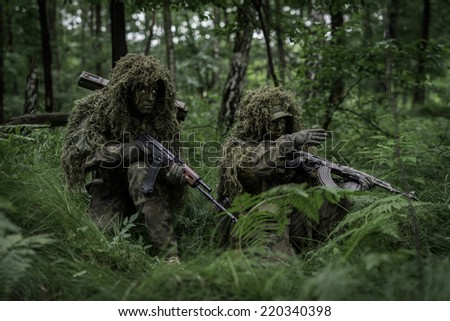 Soldiers dressed in ghillie camouflage on nature. - stock photo