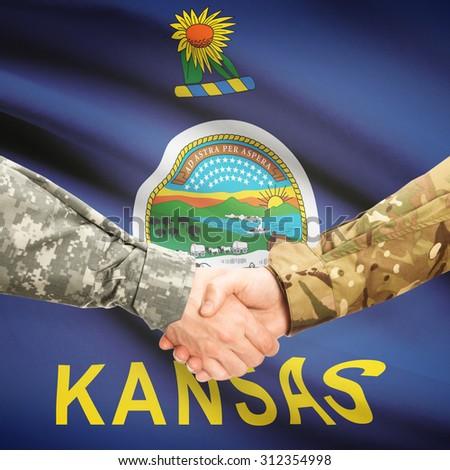 Soldiers handshake and US state flag - Kansas - stock photo