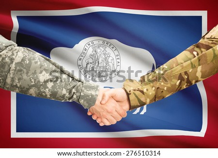 Soldiers handshake and US state flag - Wyoming - stock photo