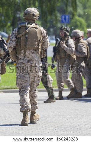 Soldiers in full gear patrol - stock photo