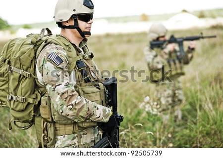 Soldiers  in full gear patrol the area in the desert - stock photo