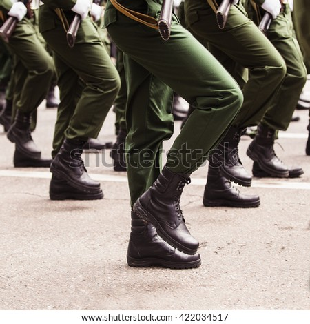 Soldiers in green dress uniform marching on the spot (a square crop)