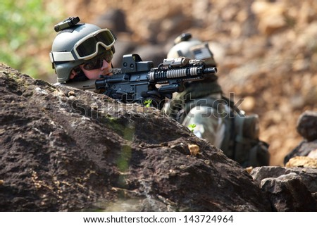 Soldiers in uniform of the U.S. Army on the battlefield - stock photo