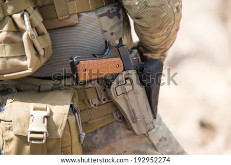 Soldiers in US Army Special Forces uniform, close up on pistol - stock photo