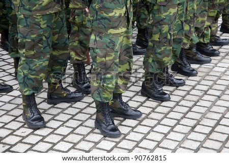 Soldiers lined up in camouflage - stock photo