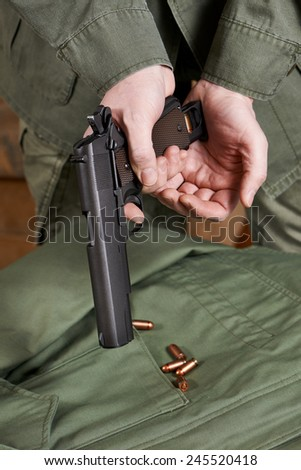 Soldiers load clip with cartridges into gun Colt closeup - stock photo