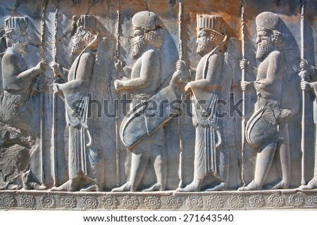 Soldiers of historical empire with weapon in hands. Stone bas-relief in ancient city Persepolis, Iran. Capital of the Achaemenid Empire (550 - 330 BC). UNESCO declared Persepolis a World Heritage Site - stock photo