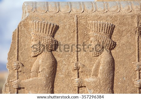 Soldiers of historical empire with weapon in hands. Stone bas-relief in ancient city Persepolis, Iran.  - stock photo