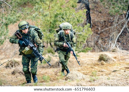 Soldiers of the Russian army march through the forest belt during a combat operation