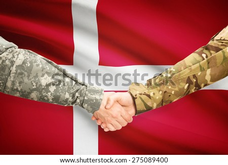 Soldiers shaking hands with flag on background - Denmark - stock photo