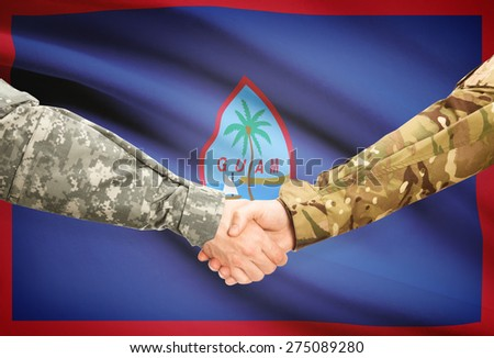 Soldiers shaking hands with flag on background - Guam - stock photo