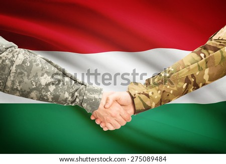Soldiers shaking hands with flag on background - Hungary - stock photo