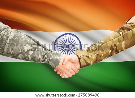 Soldiers shaking hands with flag on background - India - stock photo