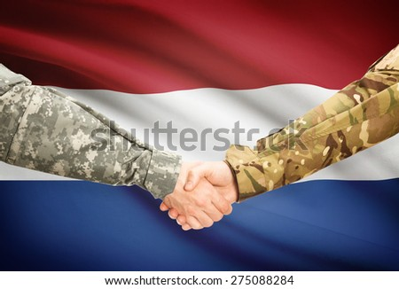 Soldiers shaking hands with flag on background - Netherlands - stock photo